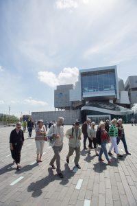 En gruppe af medlemmer af Ældresagen guides rundt af arkitekt Thomas Birket-Smith på Aalborgs havnefront. Her er gruppen ved Musikkens Hus. Foto: Jan Høst-Aaris
